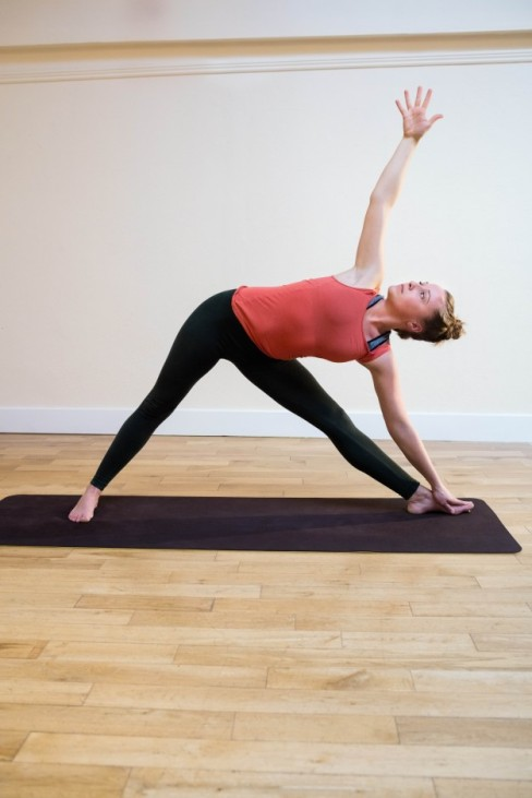woman-performing-triangle-pose-on-exercise-mat_1170-253